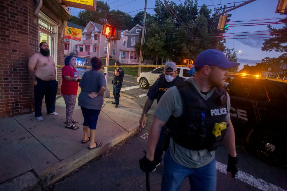 Several residents watched Meriden police investigate a shooting on Olive Street near the intersection with Crown Street Wednesday night Aug. 19, 2020. Many expressed frustration with the recent increase in shootings in the city. | Richie Rathsack, Record-Journal