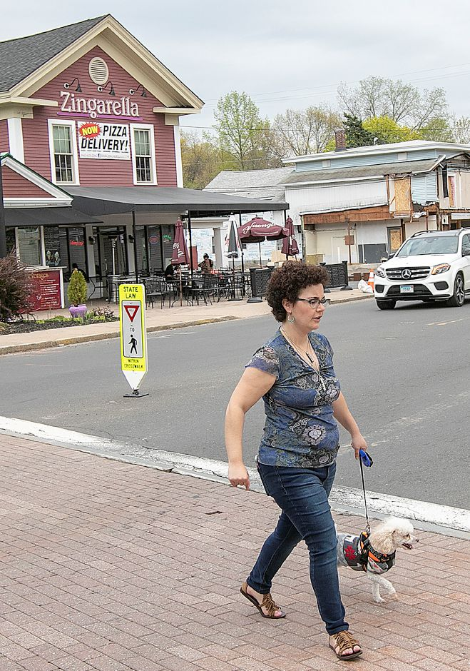 Sarena Salmeri, of Plantsville, crosses West Main Street while walking the Farmington Canal Heritage Trail with her dog, Riley,  on Thursday. Water main replacement work will begin in downtown Plantsville Monday.