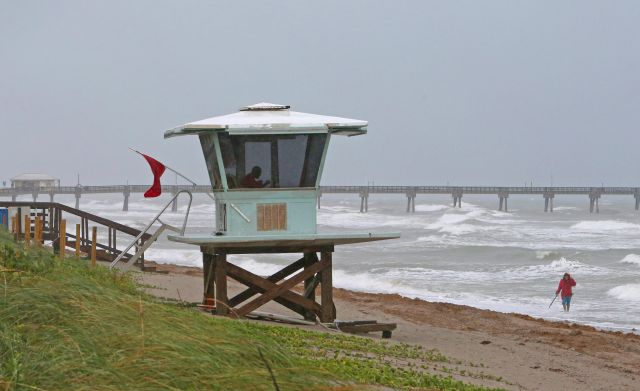 A view of the lifeguard tower while local resident Mike Squillace looking for metal at Dania Beach, Fla., as Tropical Storm Gordon pass by South Florida with wind gust and heavy rainfall for the Labor Day holiday on Monday, Sept. 3, 2018. (David Santiago/Miami Herald via AP)