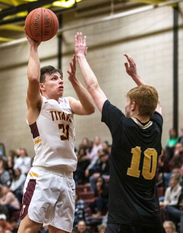 Sheehan's Garrett Molampy puts up a shot over Daniel Hand's Scott Testori during the Titans' 62-50 win at Sheehan High School in Wallingford on Friday. Before the game, Molampy received a plaque for reaching 1,000 points for his career. Aaron Flaum, Record-Journal