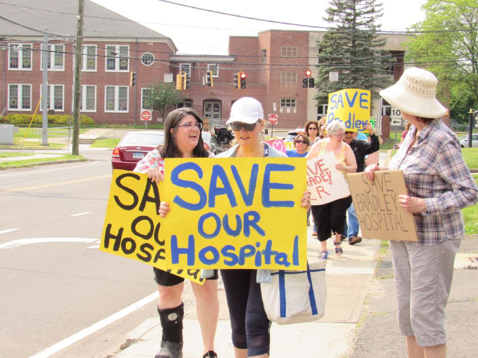 "Bonnie Sica (left) and Cheryl Pasek hold ""Save Our Hospital"" signs and lead a group from the Community Committee to Save Bradley towards the hospital in a rally, Saturday, June. 1, 2019. 