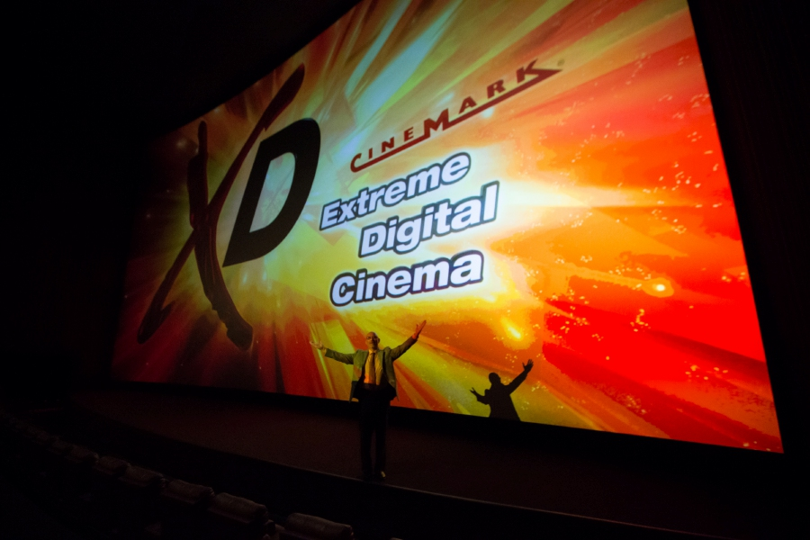 Bryan Jeffries, marketing director for Cinemark Theaters, stands in front of a movie screen during a 2015 tour of the Cinemark Theater in North Haven. The company is scheduled to reopen its theaters at Buckland Hills mall on Friday with precautions in place to prevent the spread of COVID-19. | File photo.