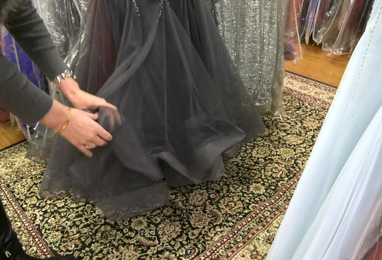 Owner Kristen Langan-Gudaitis fluffs out the bottom of a prom dress at Dynamite Designs by Kristen, 1157 N. Colony Rd. |Ashley Kus, Record-Journal