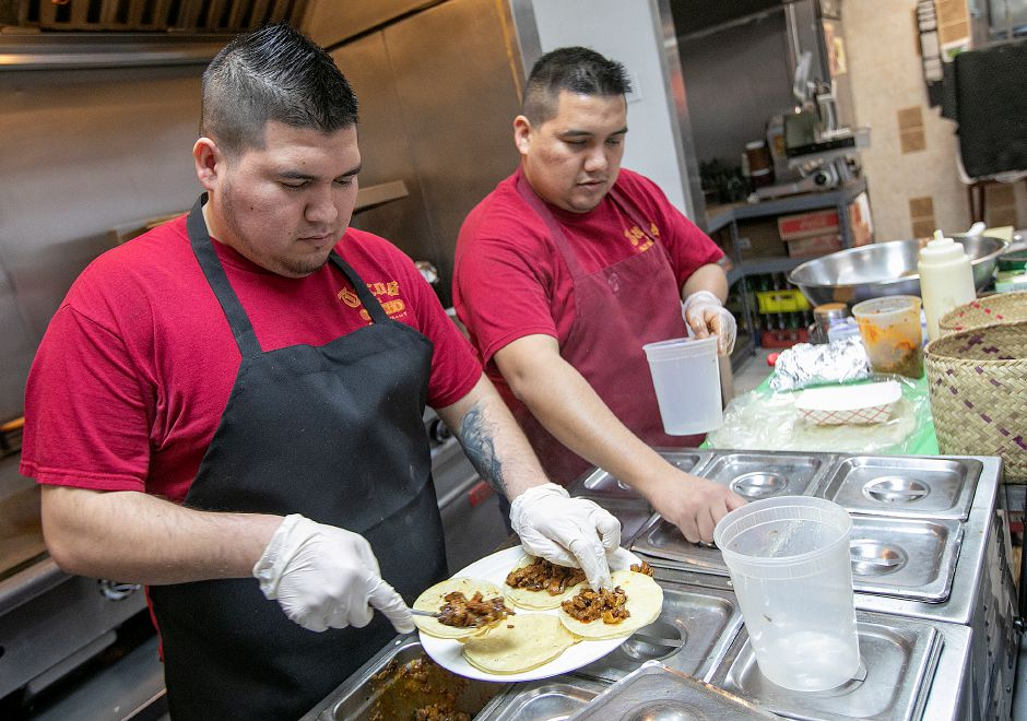 Cooks Jesus Aguilar, left, and brother, Cesar Aguilar, fill taco orders at Tacos Mi Nacho in Meriden, Thurs., Jan. 24, 2019. City officials are considering a deal to sell a vacant city-owned parcel on Broad Street to the owner of Tacos Mi Nacho, who had been looking to expand for several years. Dave Zajac, Record-Journal