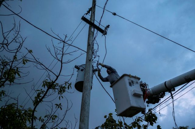 In this July 12, 2018 photo, a laborer from the Puerto Rico Power Authority works to restore power in Adjuntas, Puerto Rico. Puerto Rico