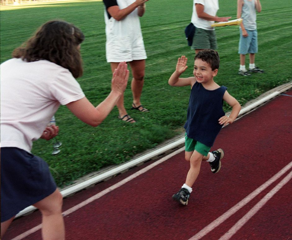 James Rolstone finishes the Fun Run held every wednsday at six-thirty at Platt High School track, July 7, 1999. he is congratulated here by his Mom, Linda.