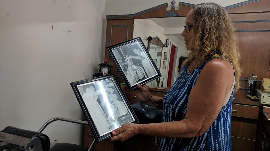 Maria Mazzacane Perez shows framed photo of her father, Joseph Mazzacone, and his U.S. Army discharge certificate, trimming a boy's hair in the 1950's at Cheshire Barber Shop's longtime location, at 1042 South Main St.  Mazzacane Perez reopened the shop at a new location this week, after it had been closed for more than two months. | Michael Gagne, Record-Journal