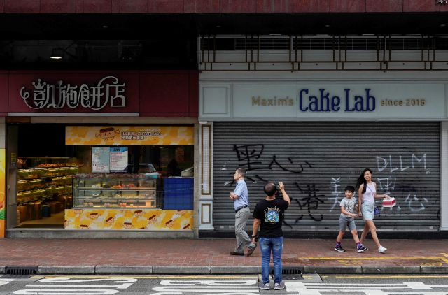 "A man takes a picture of a cake shop with protest graffiti reading ""Black heart Hong Kong Business"" in Hong Kong, Monday, Oct. 7, 2019. Two protesters were charged Monday with violating Hong Kong"