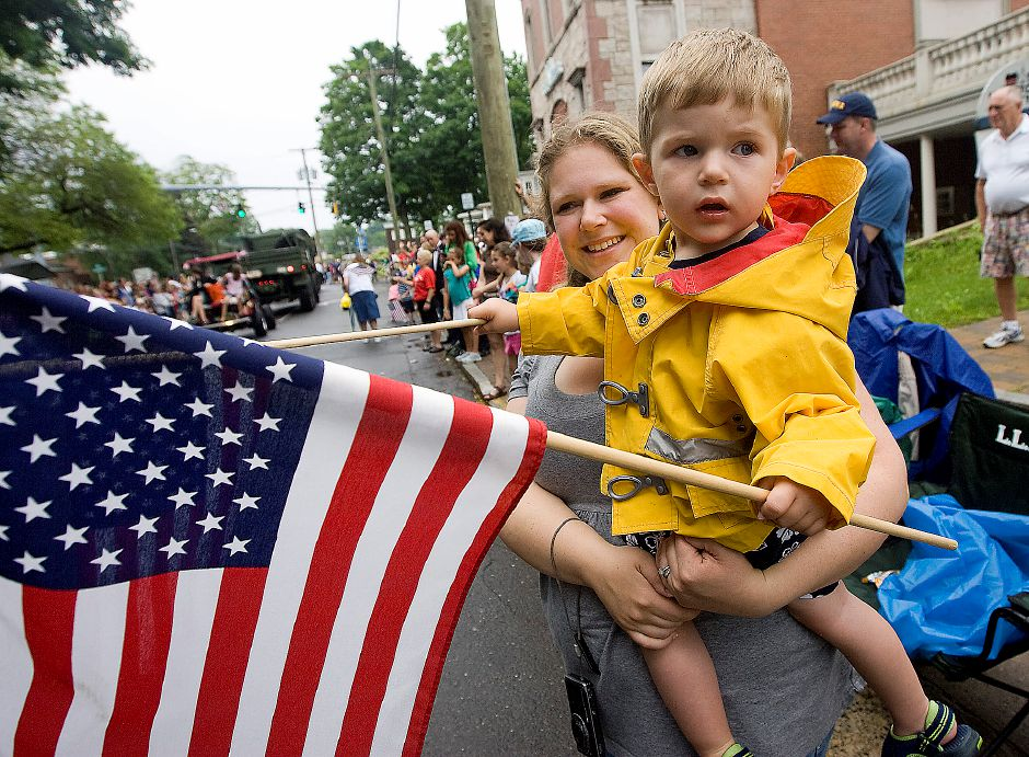 Marcie Anderson, of Kensington, holds her two year old son Connor Anderson as they watch the National Guard pass by at the Southington Memorial Day Parade in Southington on Monday May 30, 2011. Anderson