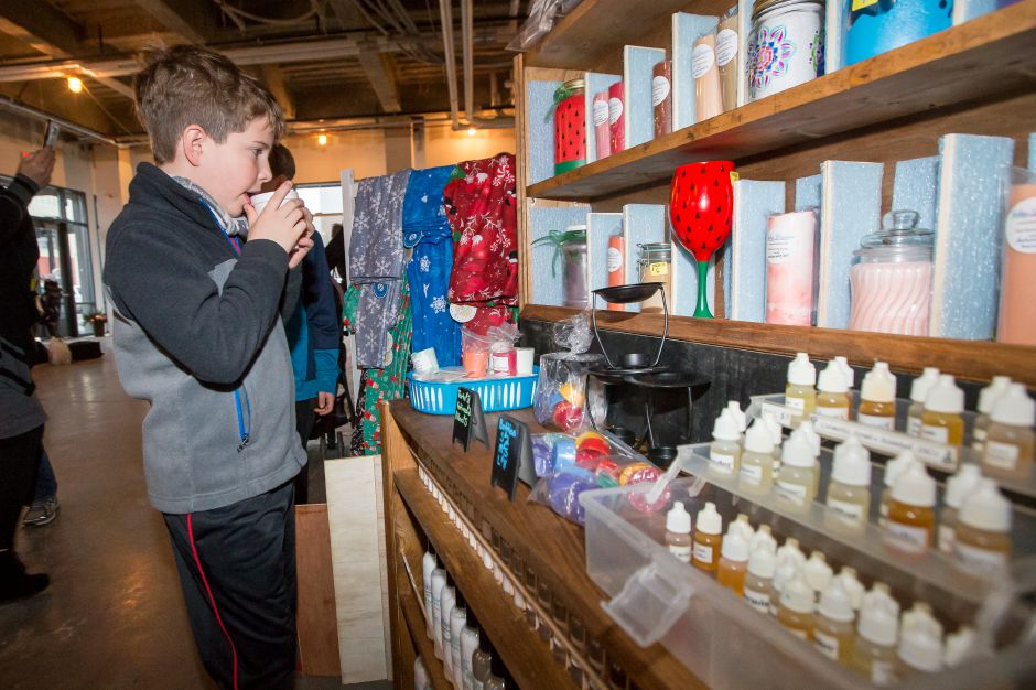 Tyler Borfiere 8 of Southington sips hot chocolate while looking at candles at a shop in 24 Colony Street Saturday during the YuleFest Meriden and Holiday Market Place on Colony Street in Meriden November 24, 2018 | Justin Weekes / Special to the Record-Journal