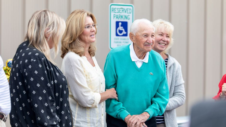 Michael Budney, in blue, celebrated his 107th birthday at the aerospace manufacturing plant he opened over 30 years ago. He continues to visit every day.   Devin Leith-Yessian/Berlin Citizen