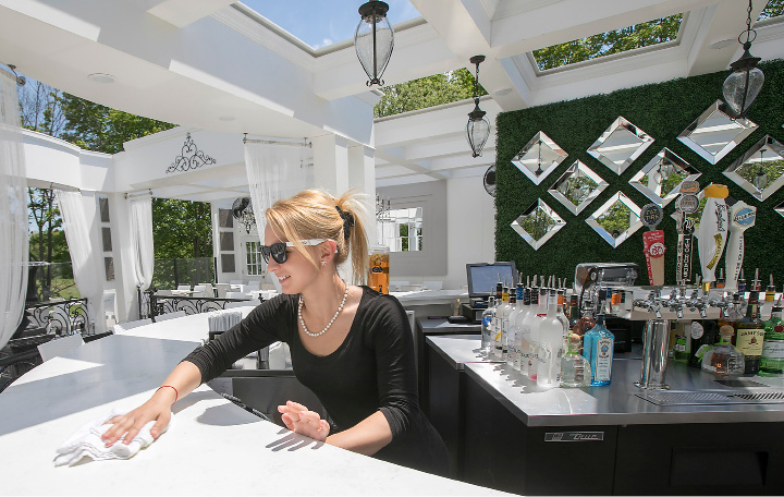 The sun shines down on bartender Danielle Grecki, of Wolcott, who prepares for customers on opening day of Cava Restaurant