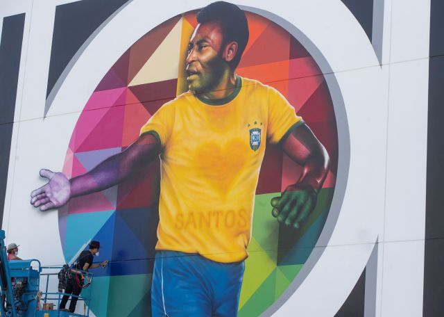 Brazilian street artist Eduardo Kobra spray paints the finishing touches to his mural to pay homage to soccer legend Pele to mark his 80th birthday in the coastal city of Santos, Brazil, Sunday, Oct. 18, 2020. Pele