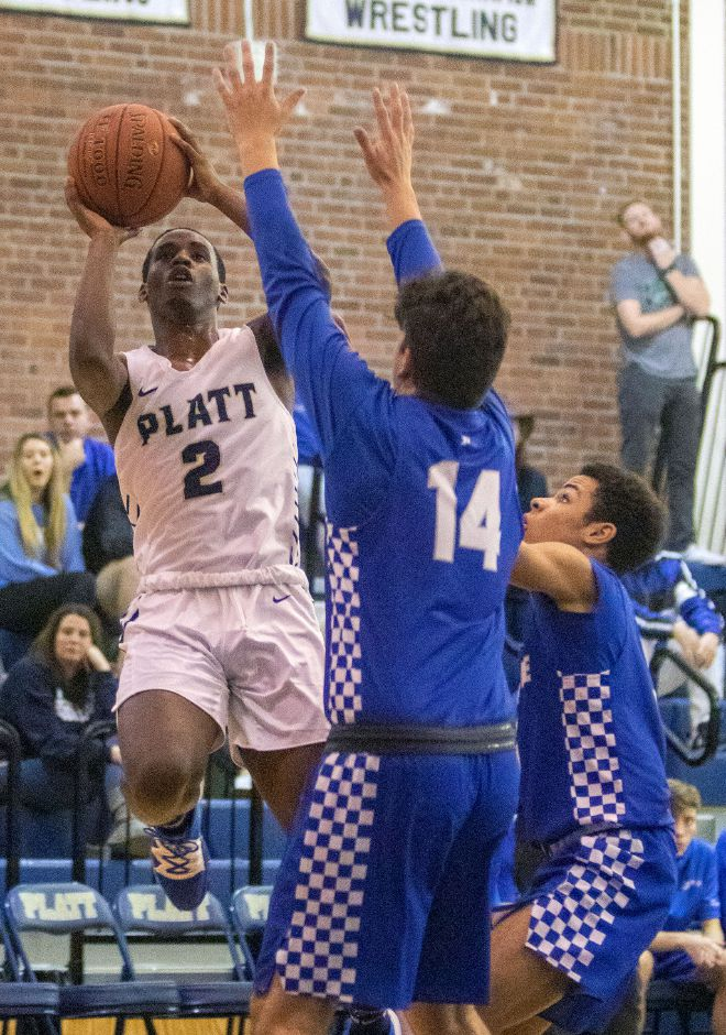 Platt's Elijah Wright goes around Plainville's Cameron Lamothe left and Javan Paradis as he goes to the basket during the first half at Platt High School on Friday, January 10, 2020. Aaron Flaum, Record-Journal