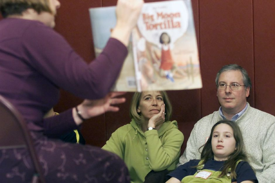 "Carrie and Steve Zerio, with their daughter Emma Zerio listen as facilitator Stacy Marcella, left, reads ""Big Moon Tortilla"" to a group of families Wed. night, jan. 24, 2001 at Nathan Hale School"