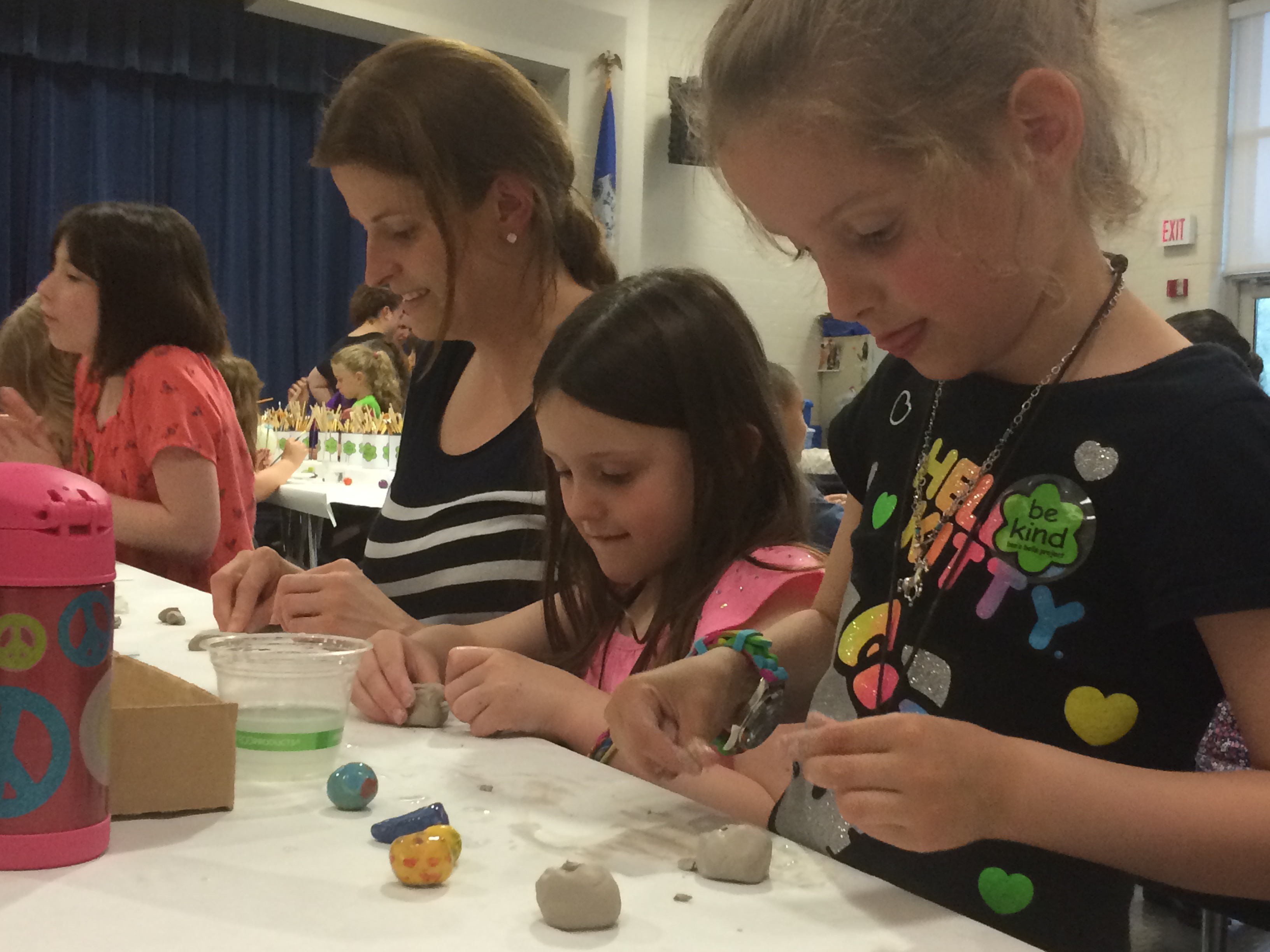 From left to right, Monika Paszkowski, Emmersyn Ceruti, and Adriana Paszkowski, both kindergarteners a Hatton School, worked on forming shapes with a ball of clay on Friday, May 16 during family night at Hatton School. | (Farrah Duffany/ Record-Journal staff).