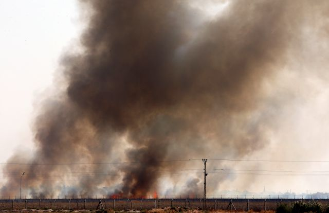 In this photo taken from the Turkish side of the border between Turkey and Syria, in Akcakale, Sanliurfa province, southeastern Turkey, smoke billows from fires on targets in Tel Abyad, Syria, caused by bombardment by Turkish forces, Sunday, Oct. 13, 2019. The United Nations says at least 130,000 people have been displaced by the fighting in northeastern Syria with many more likely on the move as a Turkish offensive in the area enters its fifth day. (AP Photo/Lefteris Pitarakis)