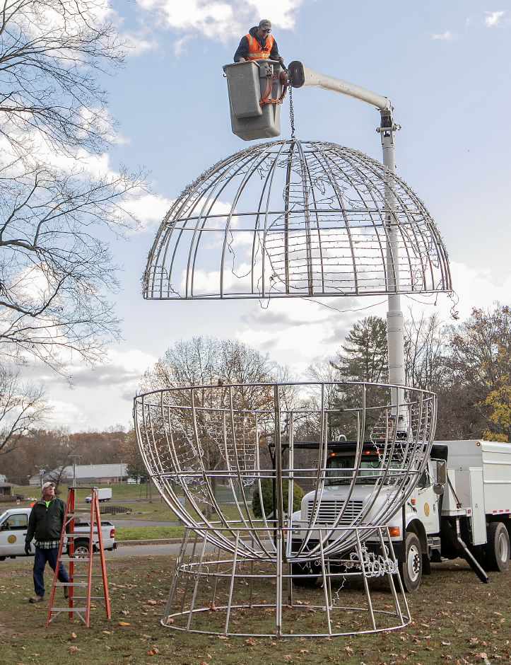 Park workers Rob Zebora, left, and Jeremy Gaj, top, assemble the Peace On Earth globe display.