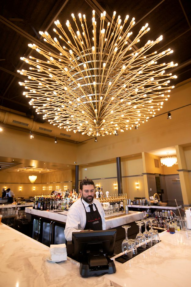 Dimitrios Zahariadis, beverage director, works at the new bar featuring a giant chandelier at the newly expanded Viron Rondo Osteria, 1721 Highland Ave., Cheshire, Nov. 13, 2019. Restaurant owner Viron Rondos acquired the chandelier through a dealer after it was taken down from a New York Film Academy theater in 2017. Dave Zajac, Record-Journal