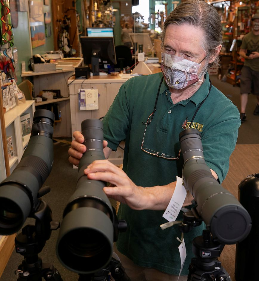 Jim Zipp, co-owner of The Fat Robin Wild Bird and Nature Shop, adjusts a scope at the Hamden business on Tuesday.