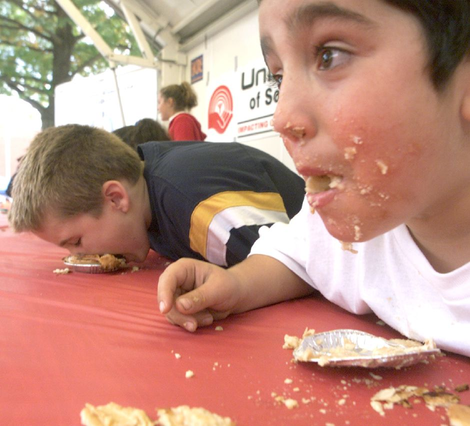 Peppe Coppola, 8, of Meriden, looks up as he comes close to finishing his apple pie during the Southington Apple Harvest Festival pie eatting contest Saturday afternoon. Coppola came close but did not win.