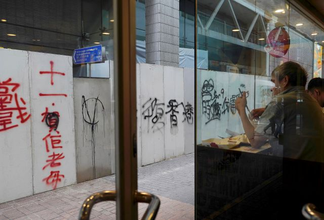 "Customers having breakfast in front of a temporary wall full of graffiti reading ""Liberate Hong Kong- revolution of our times"" in Wan Chai, Hong Kong, Monday, Oct. 7, 2019. Two protesters were charged Monday with violating Hong Kong"