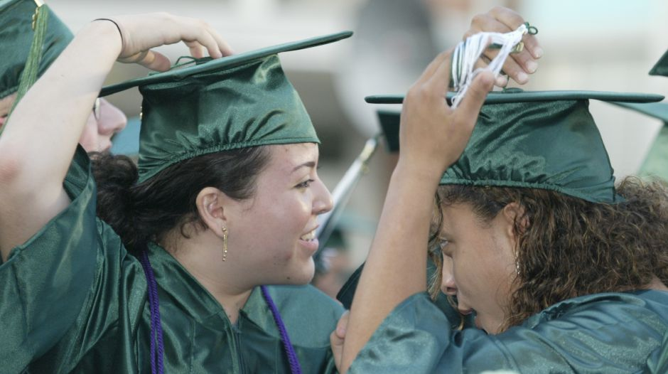 Laura Santiago, left, and Alicia Sanders remove the tassles from their caps in preparation for the tossing of the caps at Maloney High School