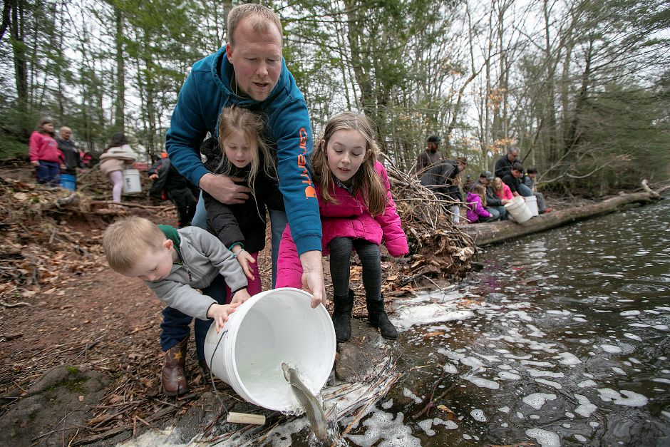 B.J. Vernon, of Meriden, and children, from left, Lucas, 3, Madison, 5, and Samantha, 8, release a brown trout into the Quinnipiac River during the annual fish stocking along the Gorge Trail in Meriden.  Dave Zajac, Record-Journal