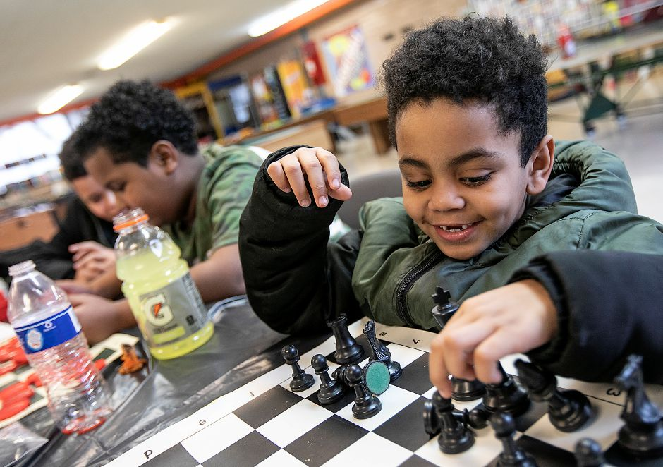 Josiyah Perez, 7, of Meriden, sets up a chess set while enjoying a week off from school at the Boys and Girls Club in Meriden on Tuesday. Meriden schools are off this  week for winter break.  Photos by Dave Zajac, Record-Journal