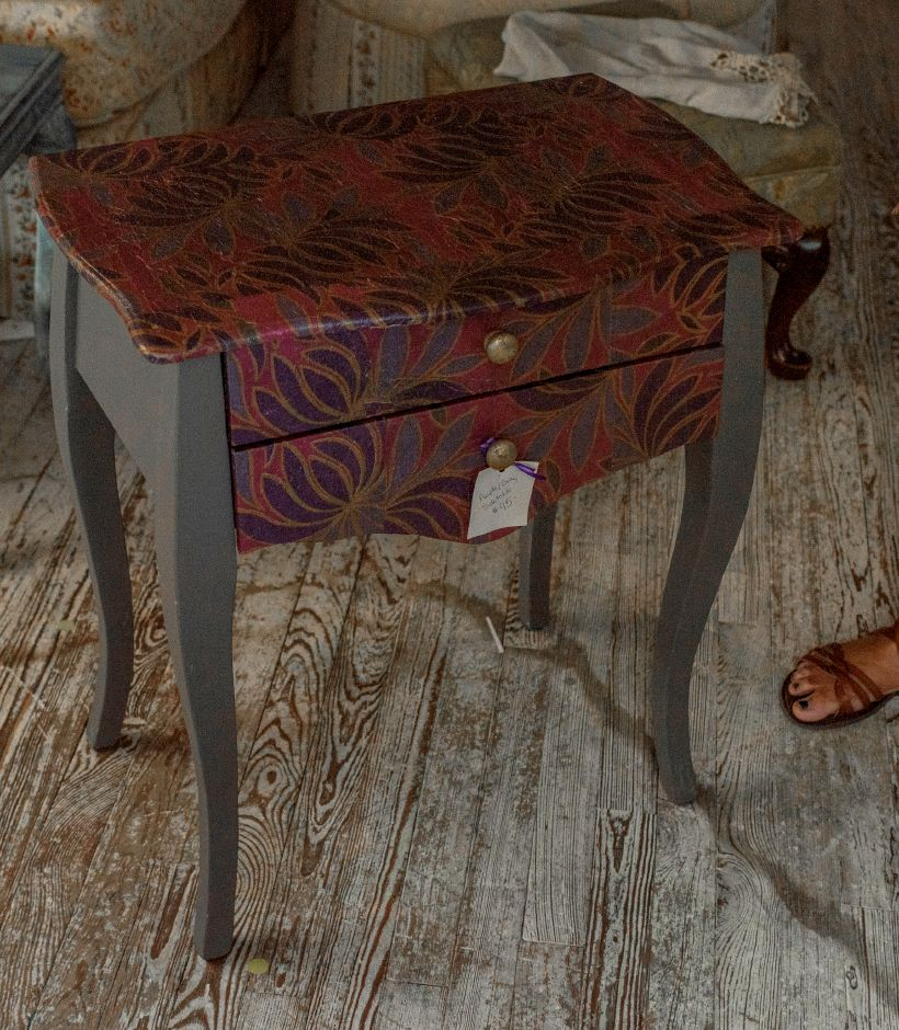 This fun, colorful side table was decorated using a grey paint and decoupaged with printed napkins by Paula Charneco, co-owner of 2 Sister