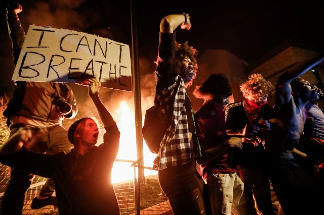 Protestors demonstrate outside of a burning Minneapolis 3rd Police Precinct, Thursday, May 28, 2020, in Minneapolis. Protests over the death of George Floyd, a black man who died in police custody Monday, broke out in Minneapolis for a third straight night. (AP Photo/John Minchillo)