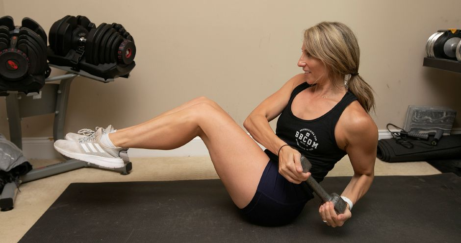 Ann Marie Svogun, of Wallingford, founder of The Fit Blonde LLC, strengthens abdominal muscles doing Russian twists at her residence, Fri., July 19, 2019. Svogun is a finalist in the United States category for an international fitness contest with a grand prize of $20,000 and a magazine spread. Dave Zajac, Record-Journal