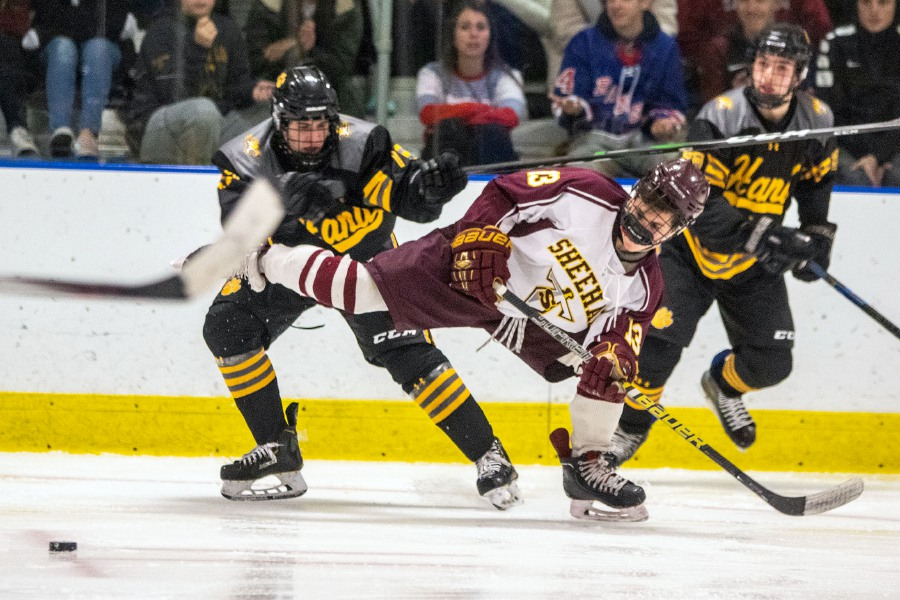 Sheehan's Luke Festa passes the puck up the ice as he is pushed by Daniel Hand's Ethan Massey during the second period at Choate Rosemary Hall in Wallingford on Wednesday. Sheehan won 6-5 in overtime.