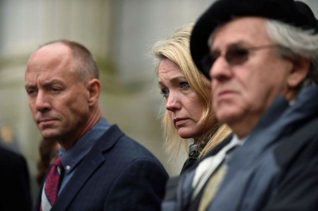 From left, Mark Barden, Nicole Hockley and Gil Rousseau listen during a press conference on the steps of the state Supreme Court after attending a hearing in a lawsuit against Remington Arms in Hartford, Conn., Tuesday, Nov. 14, 2017.   A survivor and relatives of nine people killed in the shooting are trying to sue Remington Arms, the North Carolina company that made the AR-15-style rifle used to kill 20 first-graders and six educators at Sandy Hook Elementary School. A lower court dismissed the lawsuit.  (Cloe Poisson/The Courant via AP)