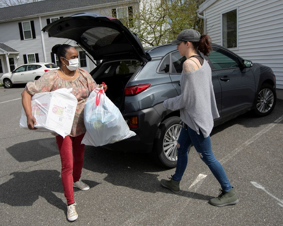 Mary Harrison, case manager, left, picks up a donation of supplies from Kaylie Chudyi, of Wallingford, at the Wallingford Emergency Shelter on  April 14. The shelter is operated by Columbus House, one of five critical providers receiving its full allotment of funding from the local United Way.