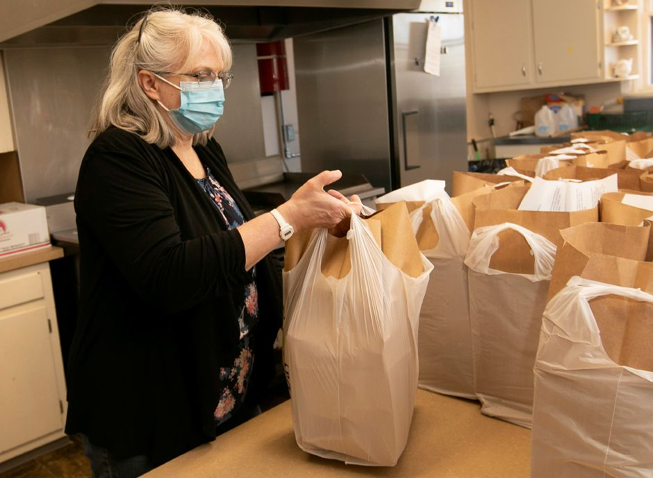 Volunteer Martha Murphy, of Meriden, adds another bag of food items for city residents enduring food insecurity at Ted's Kitchen at St Andrew