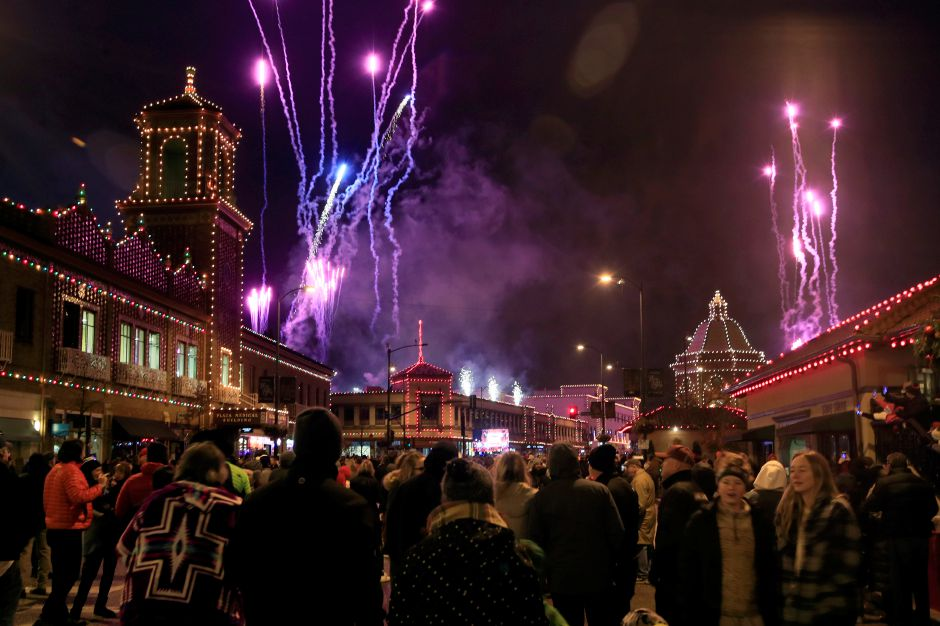 A crowd watches building lights come on as fireworks light up the sky during the Plaza Lighting Ceremony in Kansas City, Mo., Thursday, Nov. 28, 2019. The Country Club Plaza is a famous shopping district in Kansas City. This is the 90th year of the Plaza lights. (AP Photo/Orlin Wagner)