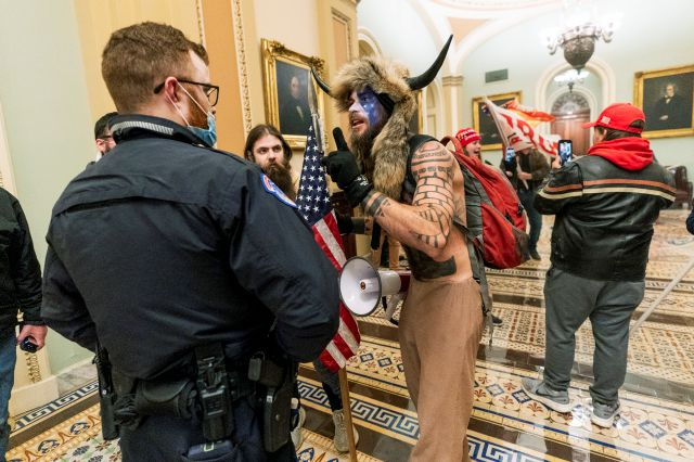 FILE - In this Jan. 6, 2021, file photo supporters of President Donald Trump are confronted by U.S. Capitol Police officers outside the Senate Chamber inside the Capitol in Washington. An Arizona man seen in photos and video of the mob wearing a fur hat with horns was also charged Saturday in Wednesday