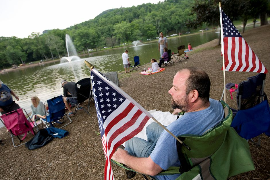 Norman Tew, of Meriden, gets an early seat in front of Mirror Lake before the start of the fireworks at Hubbard Park in Meriden, Thursday, July 2, 2015. | Dave Zajac/Record-Journal