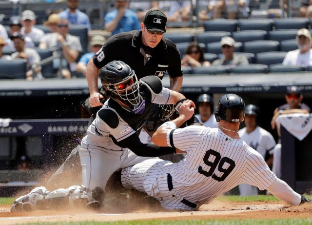 Rockies catcher Tony Wolters, left, tags the Yankees' Aaron Judge during the first inning of Saturday's game in New York as home plate umpire Chris Conroy prepares to make the out call. Associated Press