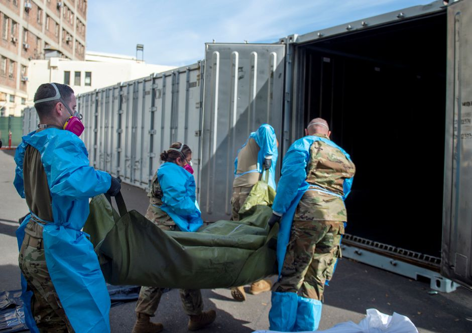 FILE - In this Jan. 12, 2021 photo provided by the Los Angeles County Department of Medical Examiner-Coroner, National Guard members assisting with processing COVID-19 deaths, placing them into temporary storage at the medical examiner-coroner