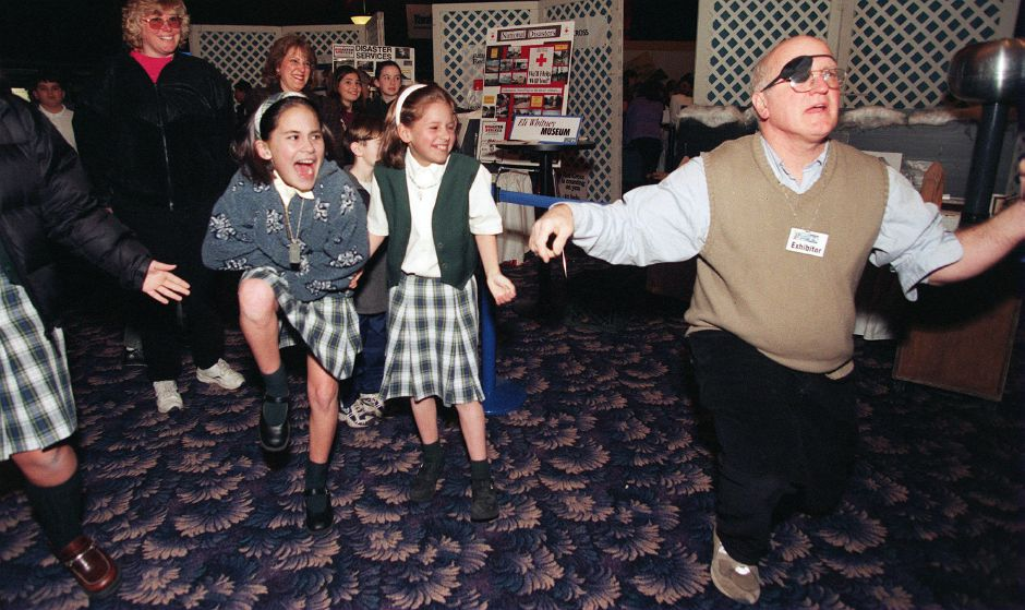RJ file photo - Caitlyn Fitzgerald, left, and Nicole Nowakowski, middle, reacts to getting a small electric shock after holding hands in a circle with Bill Brown, right, who demonstrated static conductivity, March 1999. The girls are fifth-graders at Our Lady of Mount Carmel School in Meriden.