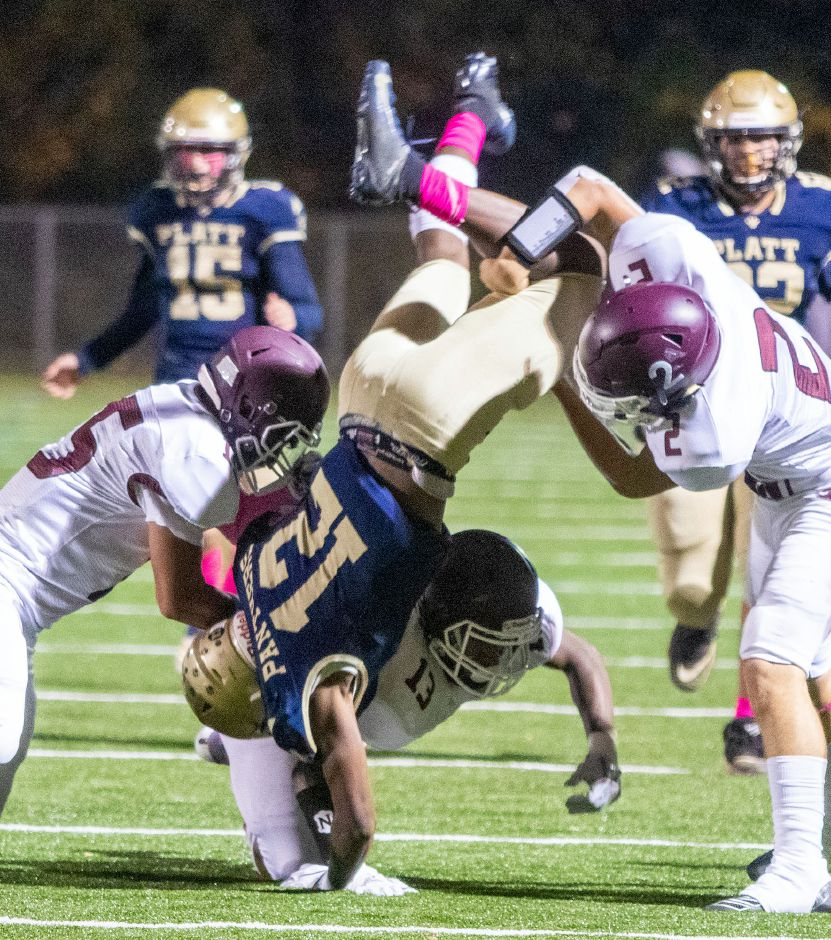 Platt's Antwone Santiago is flipped over by Bristol Central's Devin Love, Tre Jones and Victor Rosa on Friday night at Falcon Field in Meriden. Santiago made the catch and held on  for a first down. Photos by Aaron Flaum, Record-Journal