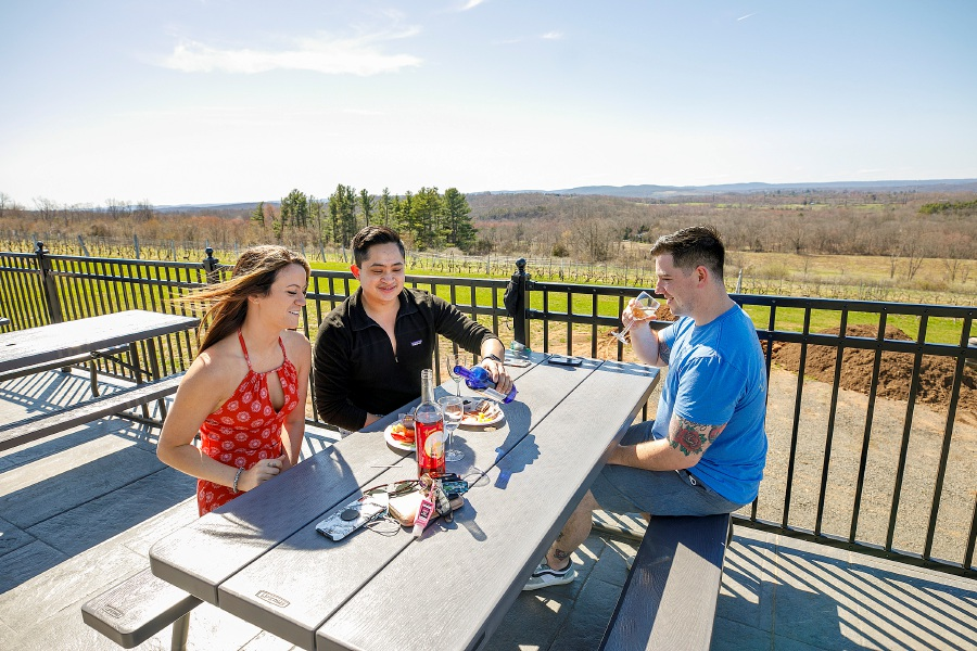 Left to right, Aubrey Tetreault, of Meriden, Jonathon Ratsombath, of West Hartford, and Ryan Finnegan, of Meriden, enjoy a glass of wine at Gouveia Vineyards in Wallingford on Wednesday afternoon. Dave Zajac, Record-Journal