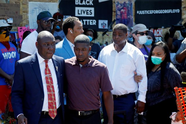 Family attorney Ben Crump, left, escorts Quincy Mason, second from left, a son of George Floyd, Wednesday, June 3, 2020, in Minneapolis, as they and some Floyd family members visited a memorial where Floyd was arrested on May 25 and died while in police custody. Video shared online by a bystander showed a white officer kneeling on his neck during his arrest as he pleaded that he couldn