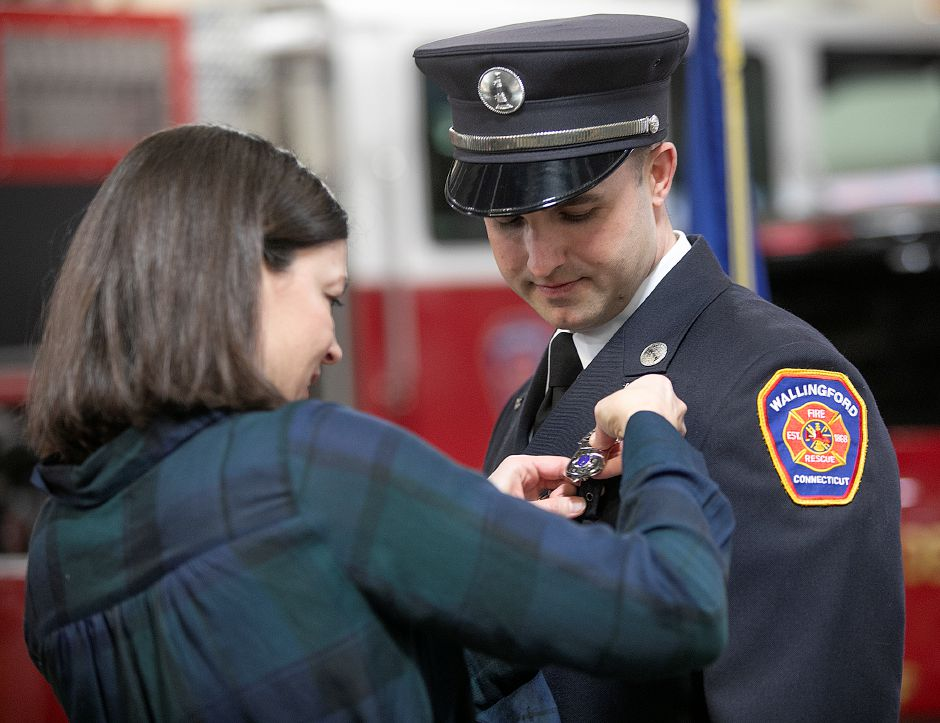 Stephanie Desjardins pins a badge for her  husband, Lt. Aaron Desjardins, after he was  sworn in during a ceremony at Wallingford Fire headquarters on  Wednesday. See more photos online at myrecordjournal.com. Photos by Dave Zajac, Record-Journal