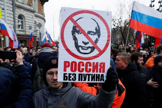 "FILE - In this Feb. 29, 2020, file photo, a man holds a banner with a portrait of Russian President Vladimir Putin, reads ""Russia without Putin"", as he attends a march in memory of opposition leader Boris Nemtsov in Moscow, Russia. Putin is just a step away from bringing about the constitutional changes that would allow him to extend his rule until 2036. The vote that would reset the clock on Putin's tenure in office and allow him to serve two more six-year terms is set to wrap up..."