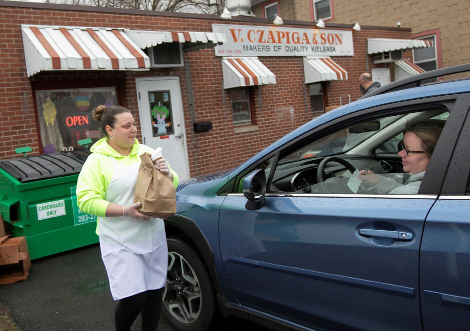 Jess Skiffington, helper, left, brings longtime customer Gina Quinn her Easter kielbasa at V. Czapiga & Son on Cooper Street in Meriden, Fri., Apr. 3, 2020. Dave Zajac, Record-Journal