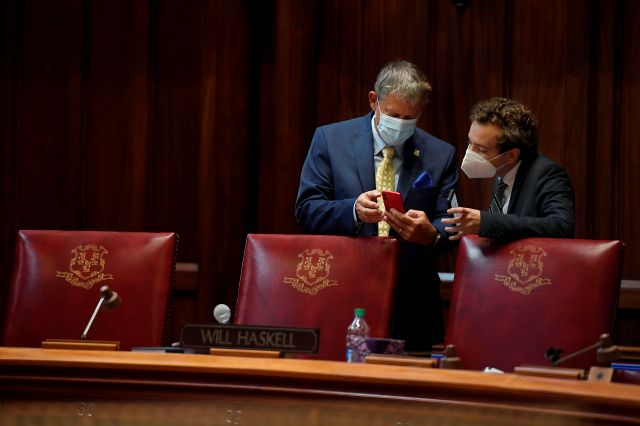 State Sen. Kevin Wilkos, R-Canton, left, talks with Sen. Will Haskell, D-Westport, right, during special session at the State Capitol, Tuesday, July 28, 2020, in Hartford. (AP Photo/Jessica Hill)