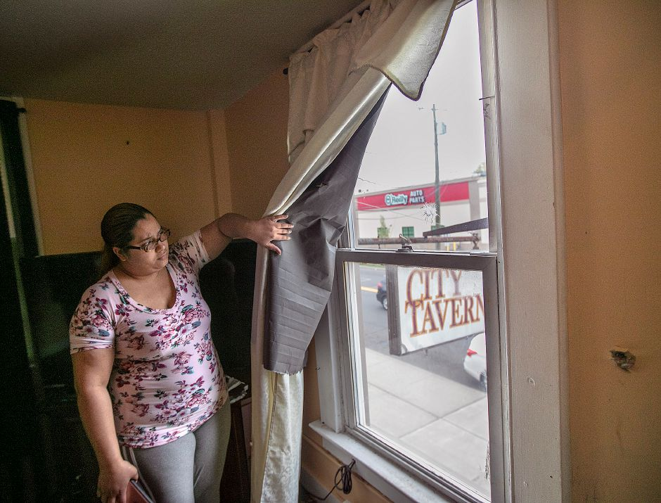 Catherine Beltran, of Meriden, shows where bullets pierced through the living room window of her residence over City Tavern on Broad Street in Meriden, Wed., May 1, 2019. Dave Zajac, Record-Journal